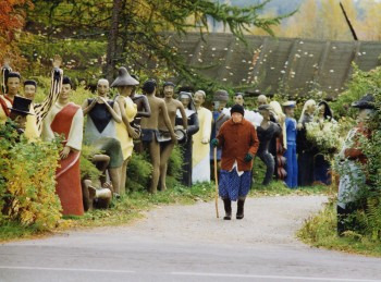 Passer-by: the artist's mother lived with him until her death. Here she walks past the carnival figures sculpted by his son – whose work she never appreciated until he began to be recognised. - Photo: Veijo Rönkkönen.
